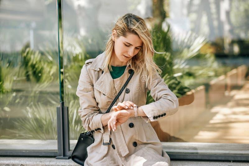 Härlig bekymrad kvinnlig som ser till klockan som väntar någon som är in sen fotografering för bildbyråer