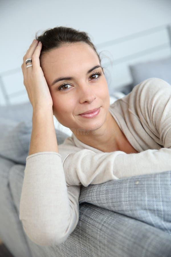 Härlig benägenhet för ung kvinna på soffan royaltyfria foton