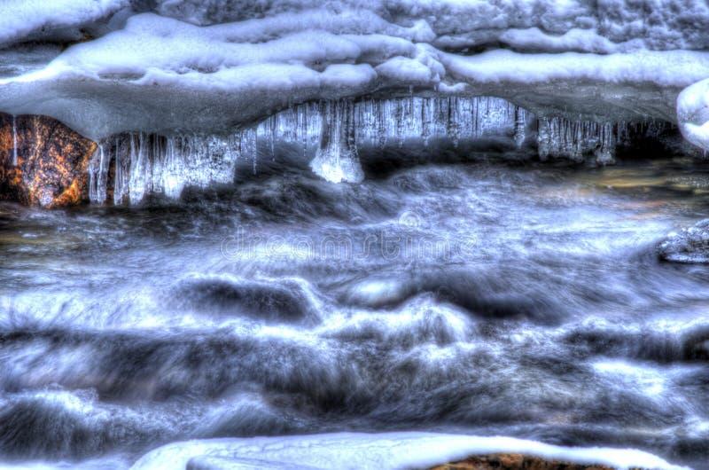 Härlig bergflodström i djupfryst vinterlandskap i den arktiska cirkeln med majestätiska långa mousserande istappar arkivfoto
