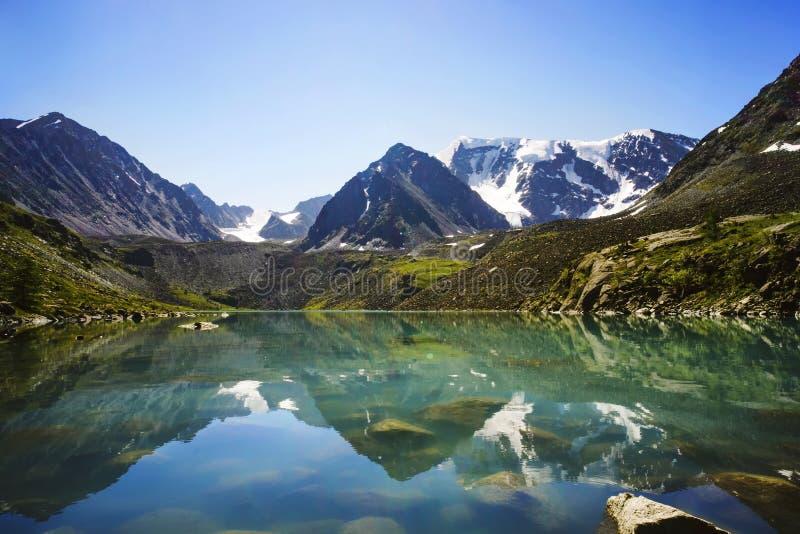 Härlig bergsjö med turkosfrikändvatten i den Altai republiken Sibirien Ryssland reflexion av berg med snö-korkat royaltyfri bild