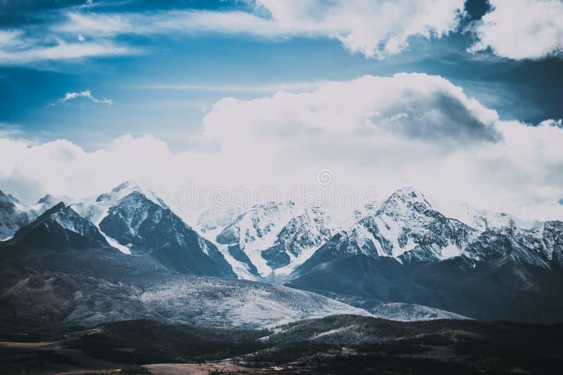 Härlig bergskedja under molnen Snöig maxima av vaggar royaltyfria foton