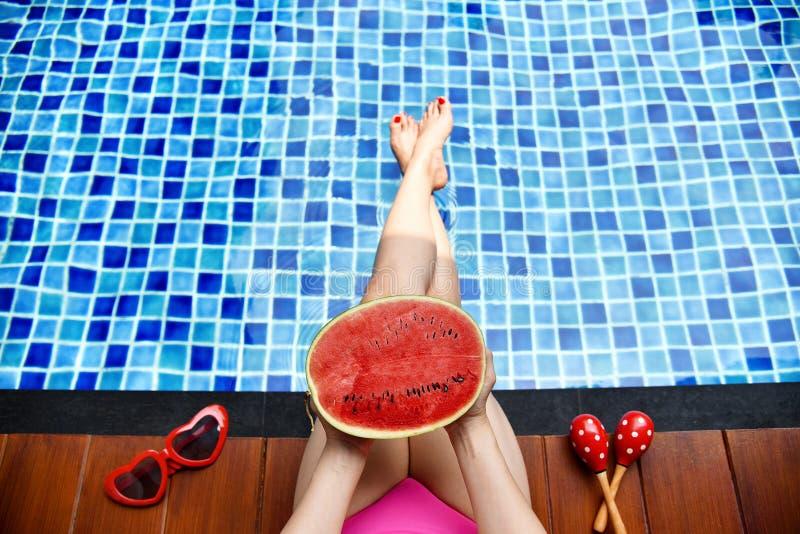 Härlig bikiniflicka som kopplar av i simbassängen, ben av kvinnan i vatten royaltyfri fotografi