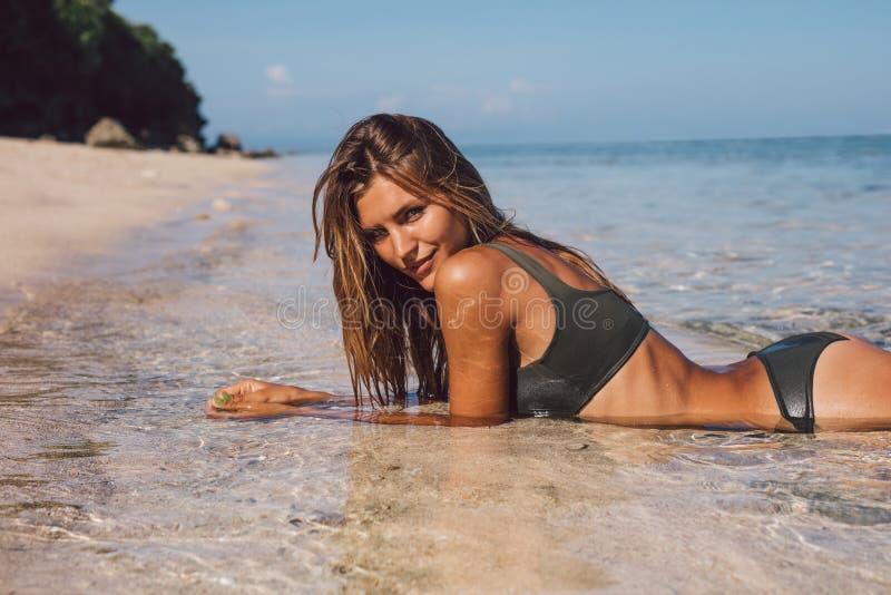 Härlig bikinimodell som kopplar av på stranden arkivfoto
