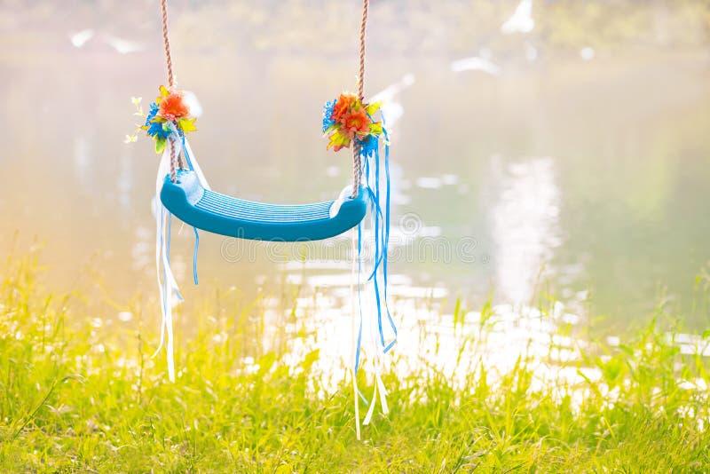 Härlig blå hängande tom gunga som göras av plast- på rep, dekorerat med blommor och band Begreppet av drömmar och royaltyfria foton