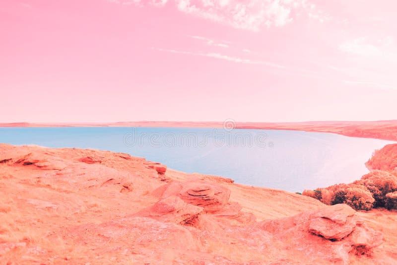 Härlig blå sjö på bakgrunden av korallkusten och rosa himmel fotografering för bildbyråer