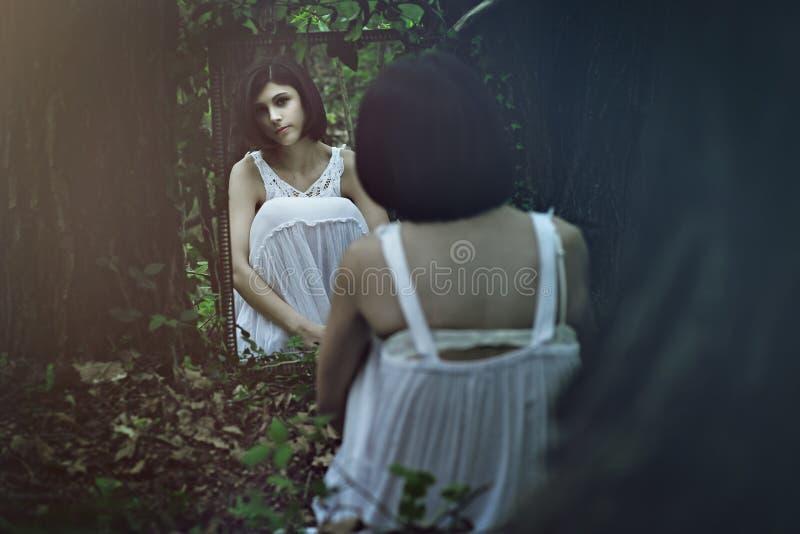 Härlig blek kvinna framme av en spegel royaltyfri foto