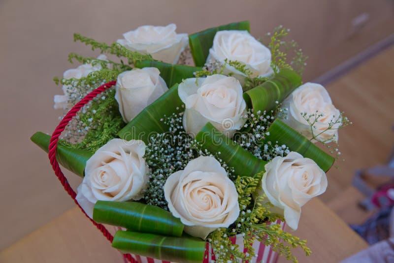 Härlig blommabukett av vita rosor i stor rund röd hattask Dag för arbetsblomsterhandlareMother ` s royaltyfria bilder
