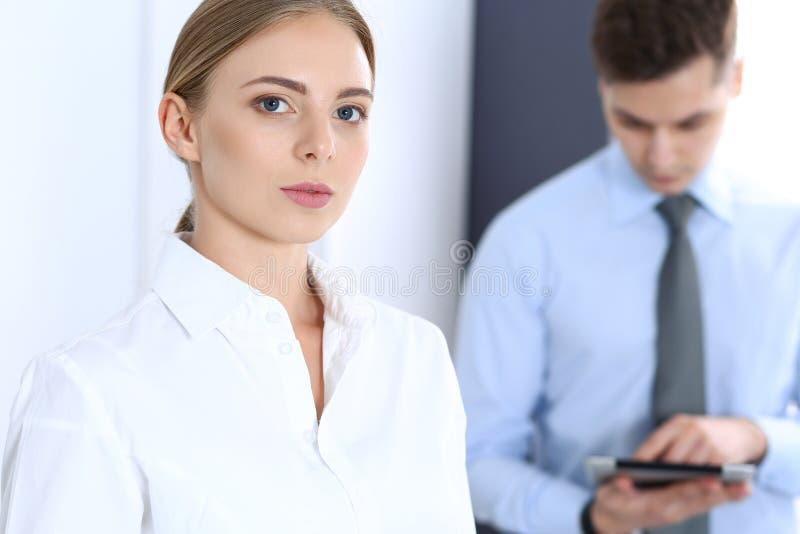 Härlig blond affärskvinna som använder minnestavlaPC, medan stå rakt i ett ljust tänt kontor äganderätt för home tangent för affä arkivfoton