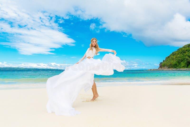 Härlig blond brud i den vita bröllopsklänningen med det stora långa drevet fotografering för bildbyråer