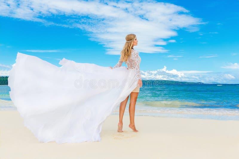 Härlig blond brud i den vita bröllopsklänningen med det stora långa drevet arkivbilder