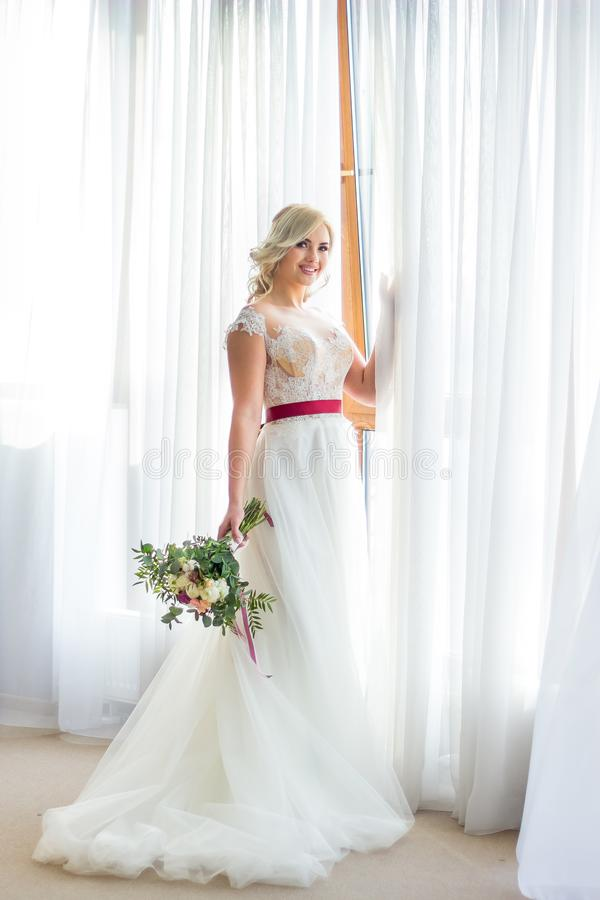 Härlig blond brud som omges av blommor Stående av en härlig flicka i en bröllopsklänning Brud i en lyxig klänning på a arkivbilder