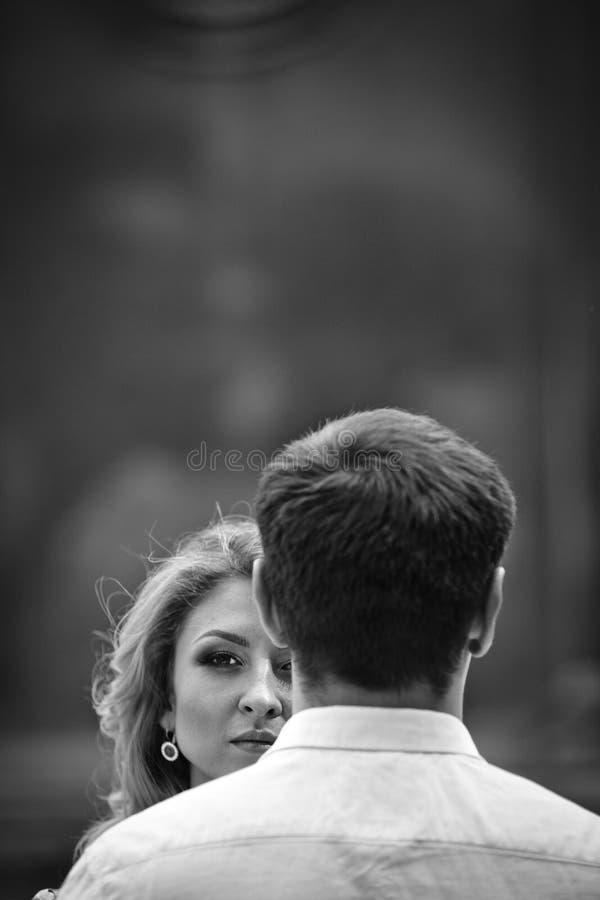 Härlig blond brud som poserar nära brudgummen, framsidacloseupb&w royaltyfri foto