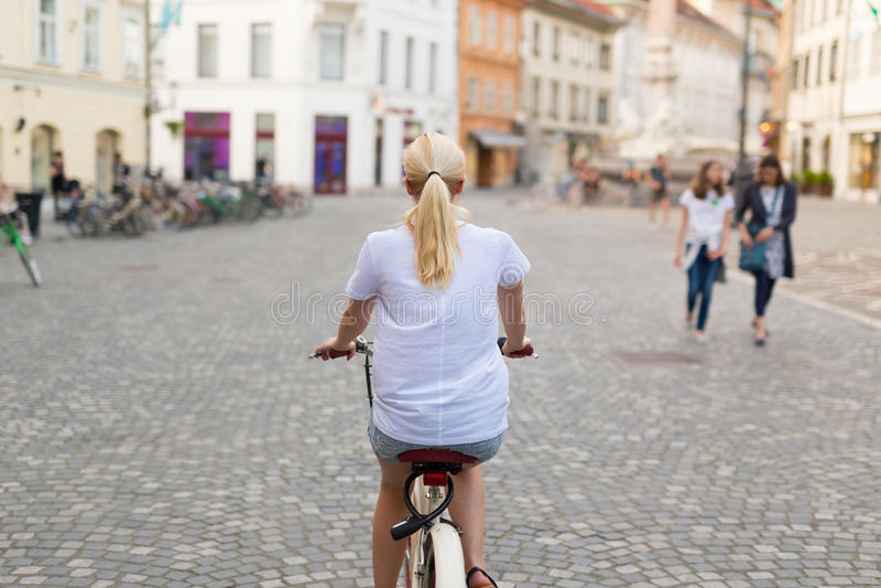 Härlig blond caucasian kvinnaridningcykel i centret arkivfoto
