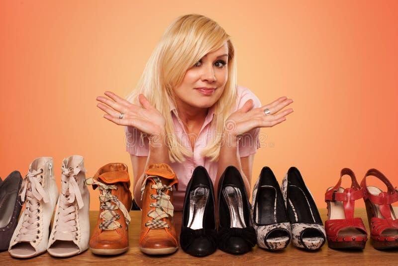 härlig blond deccision som gör skor arkivfoto