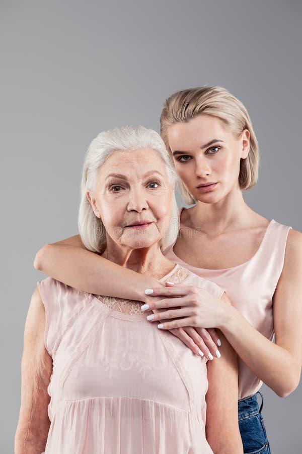 Härlig blond dotter med neutralt framsidauttryck som kramar hennes moder royaltyfri foto