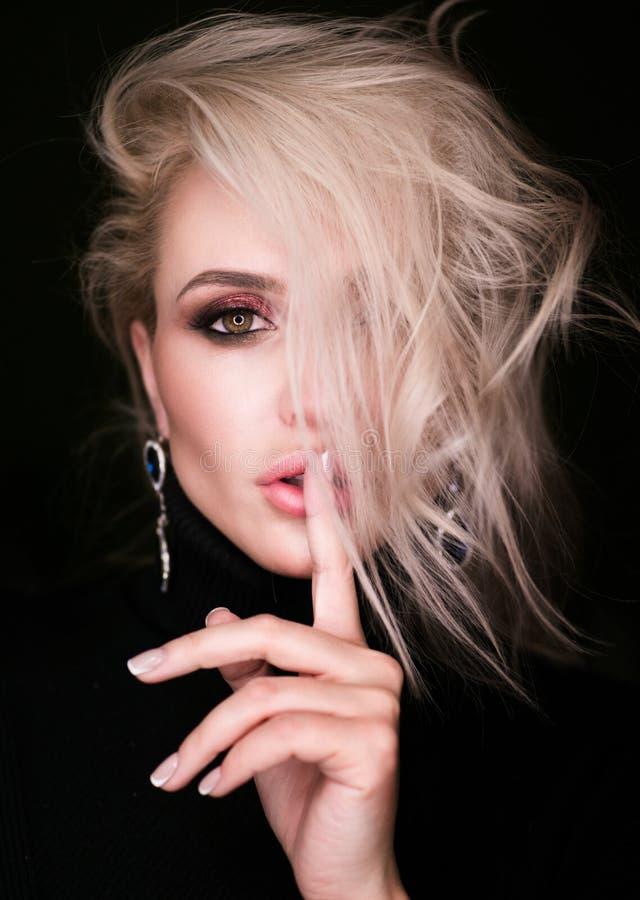 Härlig blond flicka över svart bakgrund mörker royaltyfria foton