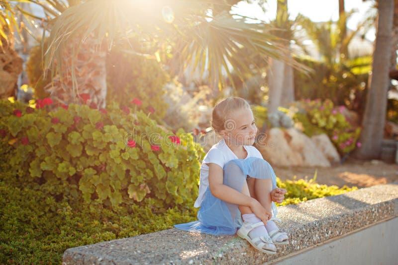 Härlig blond flicka 5 gamla år i en blå kjol som ler på fotografering för bildbyråer