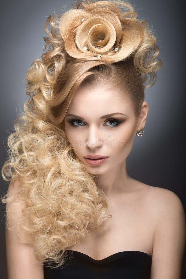 Härlig blond flicka i aftonklänning med en ovanlig frisyr i form av rosor och ljus makeup Härlig le flicka royaltyfri fotografi
