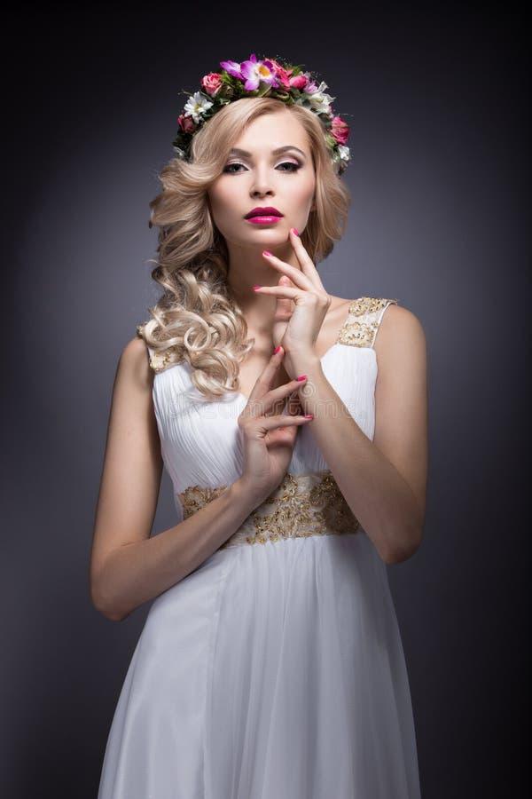 Härlig blond flicka i bilden av en brud med blommor i hennes hår Härlig le flicka arkivbild