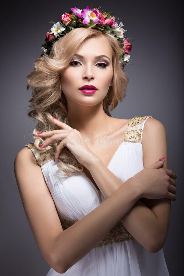Härlig blond flicka i bilden av en brud med blommor i hennes hår Härlig le flicka royaltyfri bild
