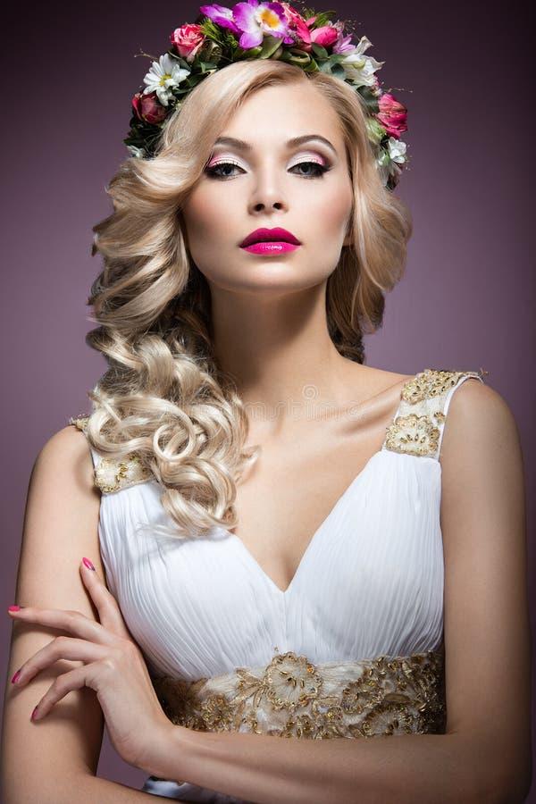 Härlig blond flicka i bilden av en brud med blommor i hennes hår Härlig le flicka white för bröllop för bakgrundsbild royaltyfri fotografi