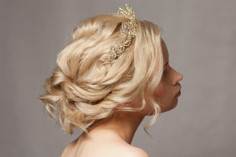 Härlig blond flicka i bilden av en brud med en tiara i hennes hår arkivfoton