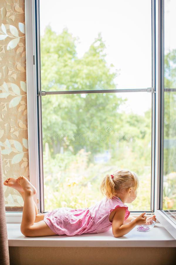 Härlig blond flicka i den rosa klänningen som hemma ligger nära stort öppet fönster på fönsterbrädan och spelar med pärlor royaltyfri foto