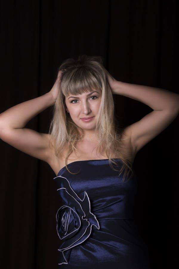 Härlig blond flicka i en blå klänning på en mörk bakgrund fotografering för bildbyråer