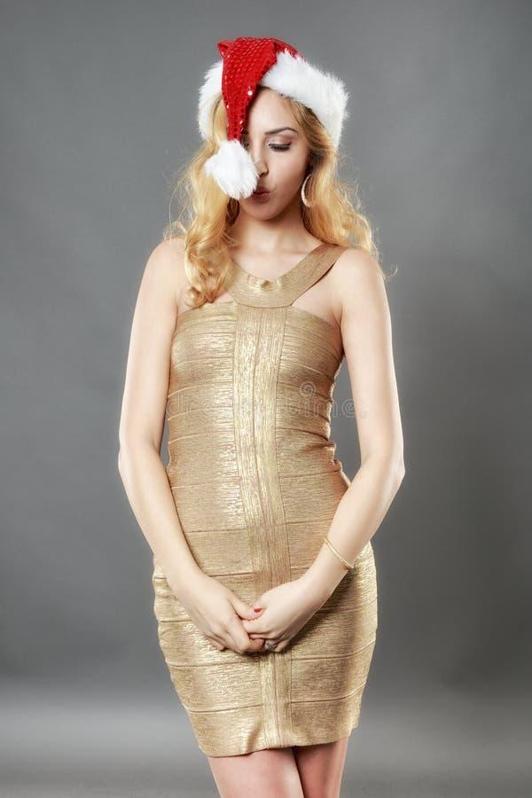Härlig blond flicka i en guld- klänning och hatt som är klara för Christma arkivfoton