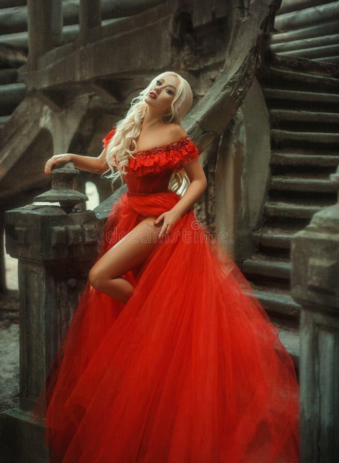 Härlig blond flicka i en lyxig röd klänning arkivfoton