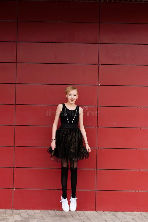 Härlig blond flicka i en svart klänning som poserar mot en röd vägg royaltyfri fotografi