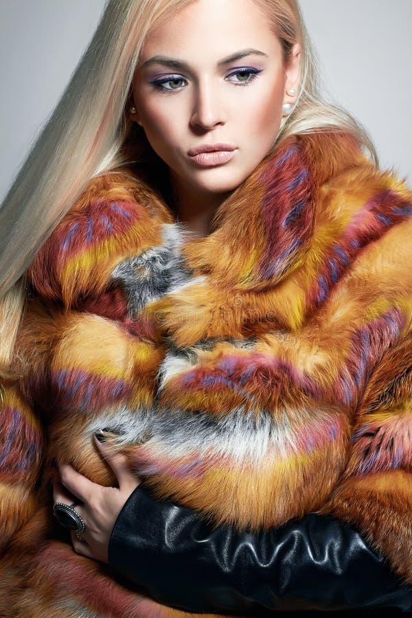 Härlig blond flicka i färgrik päls royaltyfri bild