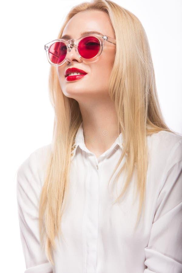 Härlig blond flicka i rosa exponeringsglas och skjorta Härlig le flicka bakgrund isolerad white royaltyfria bilder