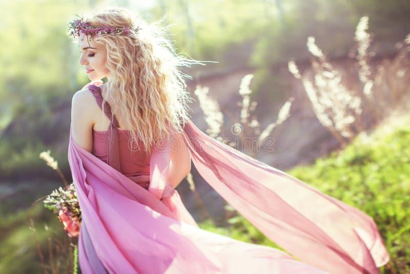 Härlig blond flicka i rosa lång klänning royaltyfri foto