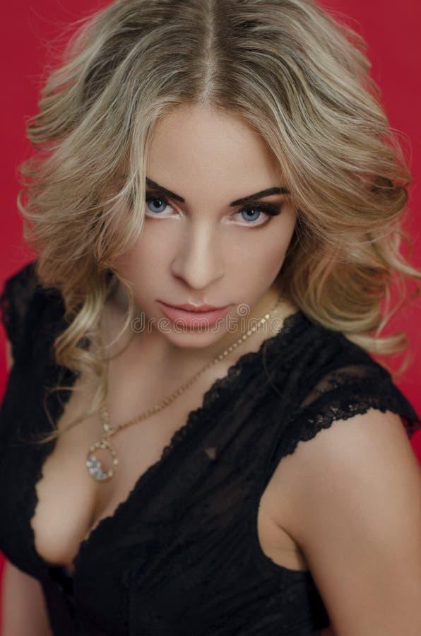 Härlig blond flicka i svart klänning royaltyfri bild