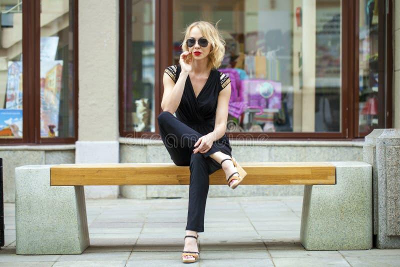 Härlig blond flicka i svart klänningsammanträde på en bänk i summe arkivfoton