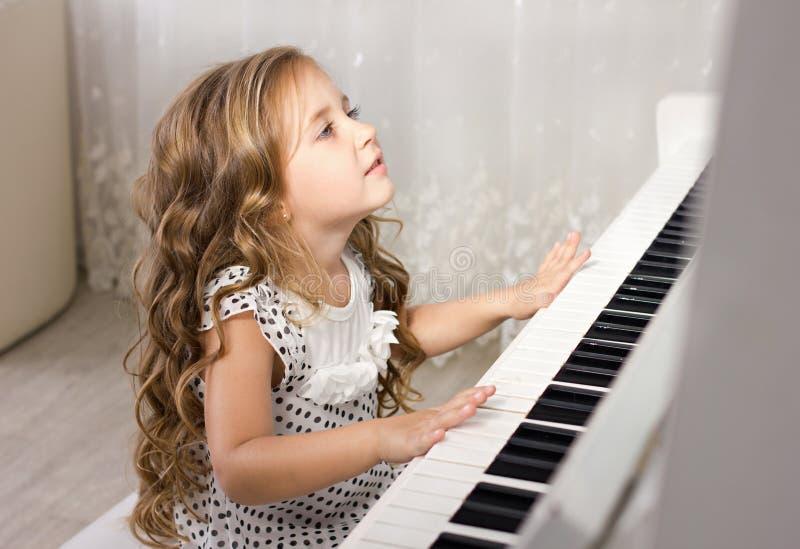 härlig blond flicka little leka för piano arkivbild