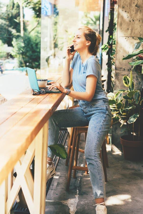 Härlig blond flicka med en bärbar dator i ett kafé arkivfoto
