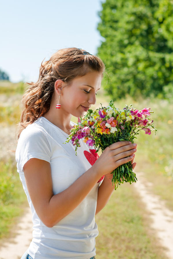 Härlig blond flicka med en bukett av lösa blommor utomhus arkivfoton