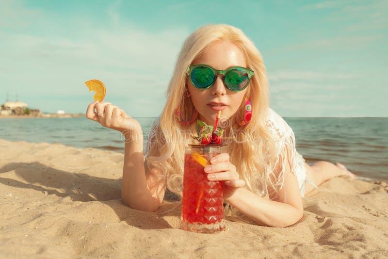 Härlig blond flicka med en röd härlig coctail i hennes händer vid havet/floden royaltyfri fotografi