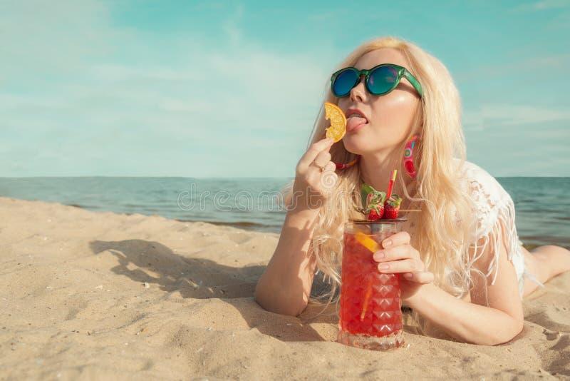 Härlig blond flicka med en röd härlig coctail i hennes händer vid havet/floden arkivfoton