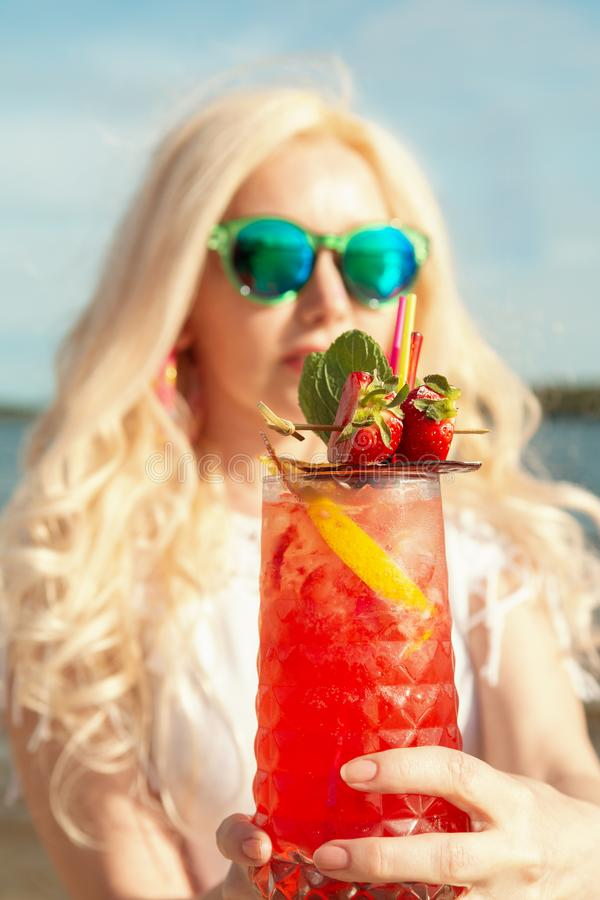 Härlig blond flicka med en röd härlig coctail i hennes händer vid havet/floden royaltyfri foto