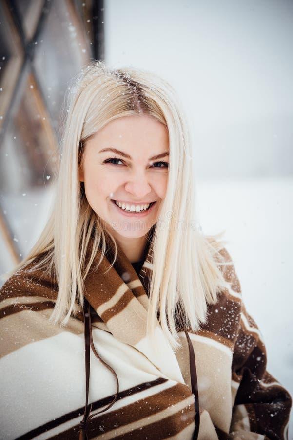 Härlig blond flicka med en tappningkamera som ler mot bakgrunden av ett vinterlandskap royaltyfria foton