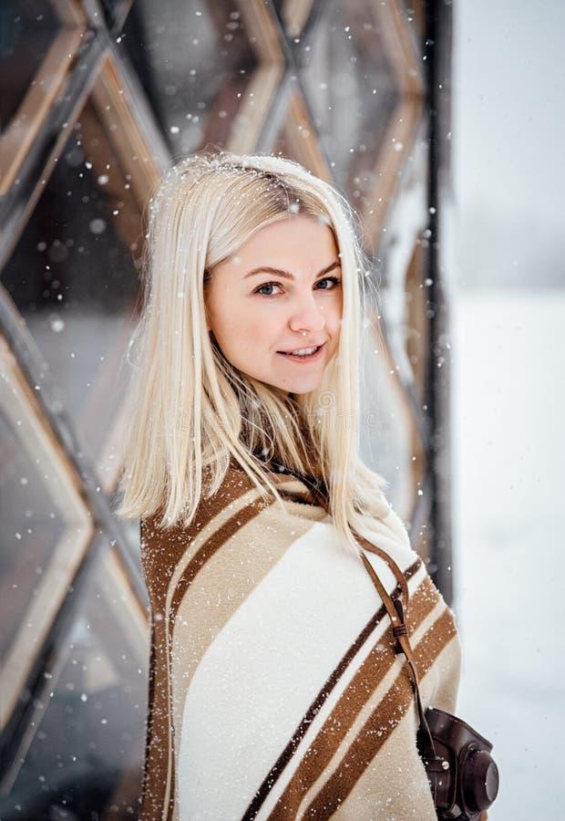 Härlig blond flicka med en tappningkamera som ler mot bakgrunden av ett vinterlandskap royaltyfri bild