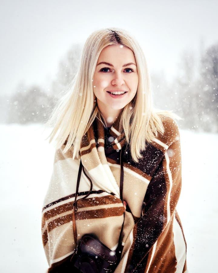 Härlig blond flicka med en tappningkamera som ler mot bakgrunden av ett vinterlandskap arkivbilder