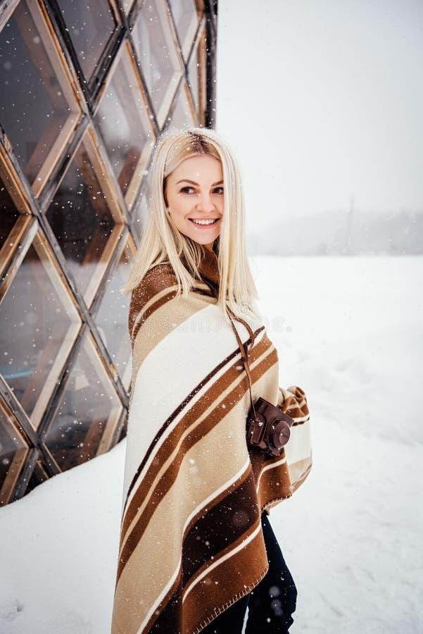 Härlig blond flicka med en tappningkamera som ler mot bakgrunden av ett vinterlandskap royaltyfria bilder