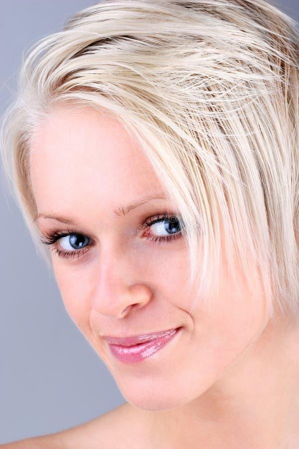 Härlig blond flicka med ett älskvärt leende royaltyfria foton