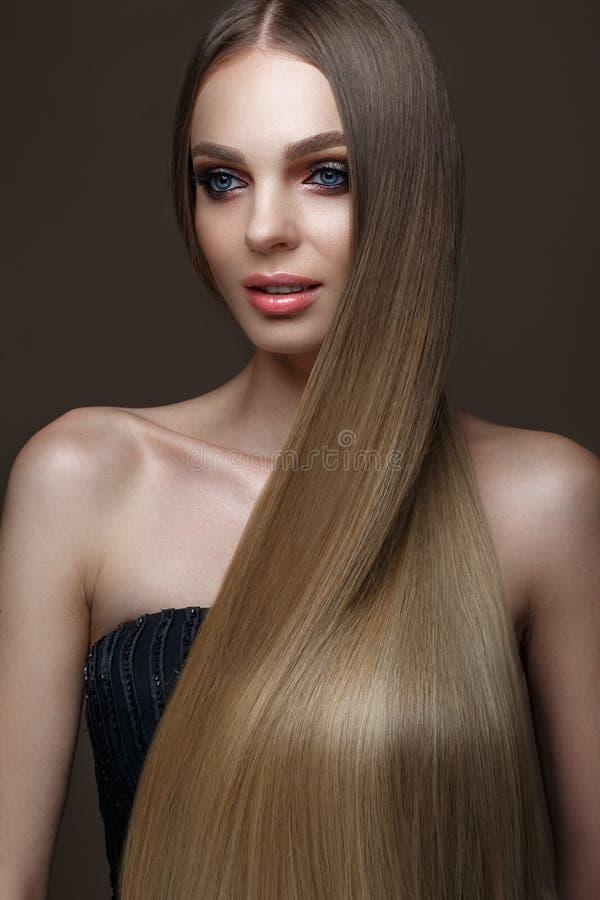 Härlig blond flicka med ett perfekt slätt hår, klassiskt smink Härlig le flicka arkivbilder