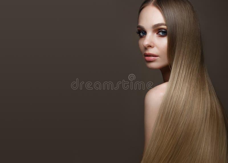 Härlig blond flicka med ett perfekt slätt hår, klassiskt smink Härlig le flicka royaltyfri bild