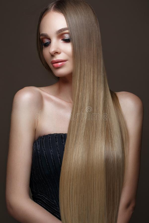 Härlig blond flicka med ett perfekt slätt hår, klassiskt smink Härlig le flicka royaltyfri fotografi